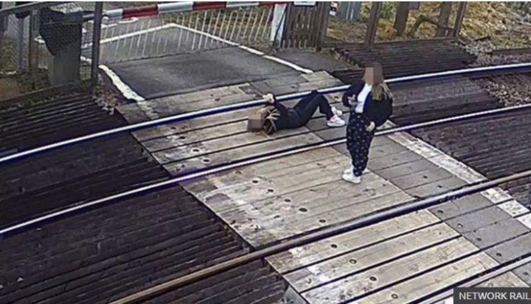 Çudia në Britani, vajza qëndron e shtrirë me telefonin në dorë në shinat e trenit